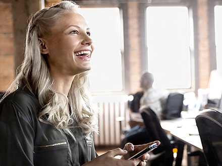 Women laughing while holding her smart phone